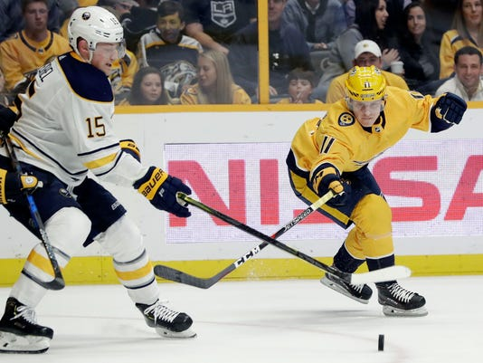 Buffalo Sabres center Jack Eichel (15) and Nashville Predators right wing Eeli Tolvanen (11), of Finland, reach for the puck in the first period of an NHL hockey game Saturday, March 31, 2018, in Nashville, Tenn. (AP Photo/Mark Humphrey)