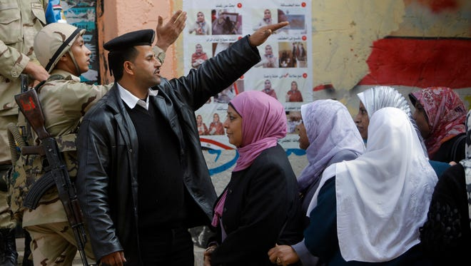 An Egyptian army soldier and a policeman direct voters in front of a polling station in Cairo on Jan. 14, 2014.