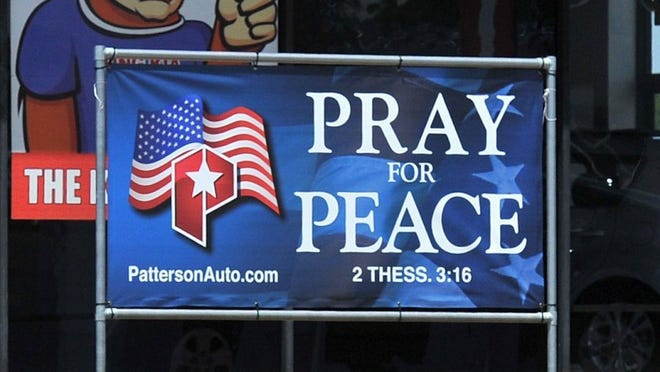 CHRISTOPHER WALKER/TIMES RECORD NEWS A sign outside the Patterson Kia dealership reads: Pray for Peace. The message from the car dealer has been showing up in billboards and yard signs recently.