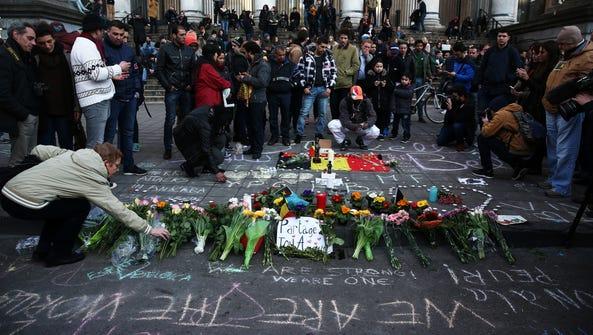 People leave tributes at the Place de la Bourse following