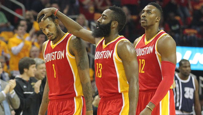James Harden, middle, pats forward Trevor Ariza on the head during a Oklahoma City Thunder timeout in the first quarter at Toyota Center.