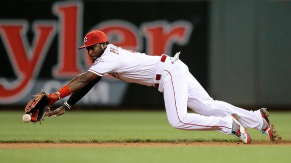 Reds second baseman Brandon Phillips dives but is unable to catch a ground ball off the bat of Giants center fielder Denard Span on Monday night.