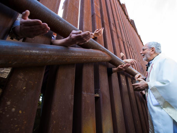 Bishop Gerald Kicanas of the Tucson Diocese offers Communion on Tuesday through the border fence to people in Mexico as part of a Mass in Nogales, Ariz., coordinated by the U.S. Conference of Catholic Bishops.