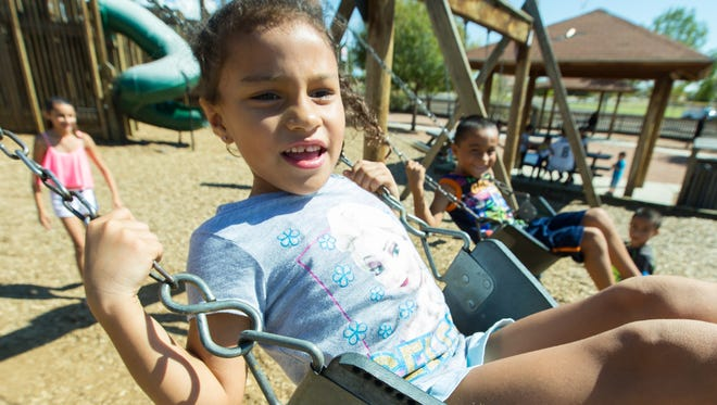 """Brianna Sotelo, 6, of Las Cruces, plays on the swings with her family at Unidad Park on Monday, Oct., 10, 2016, during a day off from school to recognize Columbus Day. Behind Sotelo, from left, is Brittany Barajas, 12, Andrew Sotelo, 6, and Brian Sotelo, 7. """"We have been playing outside all weekend, the weather has been good,"""" Barajas said."""