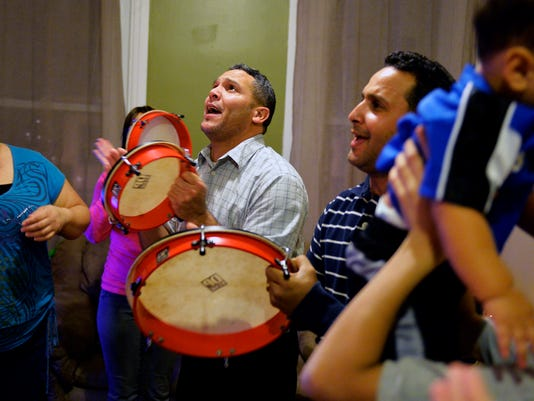 Brothers Carlos and Jorge Montalvo, along with Carlos's daughter Karla, beat on las plenas (drums) as they and other relatives sing traditional Puerto Rican, parrandas-style Christmas music in Carlos's living room on Thursday, Dec. 20, 2013. Jorge Montalvo and his brother Carlos came to York from Puerto Rico about 14 years ago, and have since lived in the city with their families. Every Christmas, their 12 other siblings and other relatives fly up from Florida, Puerto Rico and other areas to celebrate the holiday in a hotel ballroom that they rent to hold more than 100 people. The Montalvo brothers and their families also regularly gather at least twice a month for large family dinners featuring traditional Puerto Rican food. Chris Dunn -- Daily Record/Sunday News
