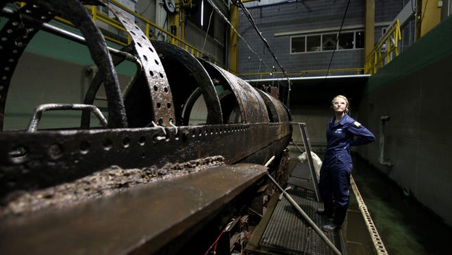 Conservator Anna Funke stands next to the H.L. Hunley in the Warren Lasch Conservation Center in North Charleston, S.C., Wednesday, June 7, 2017. For years, two scientists have been painstakingly cleaning a century and a half of sand, sediment and corrosion from the first submarine in history to sink an enemy warship.