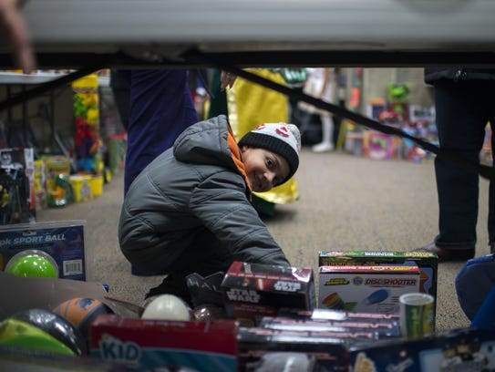 Angel Sosa, 4, browses a room full of toys as the Puerto