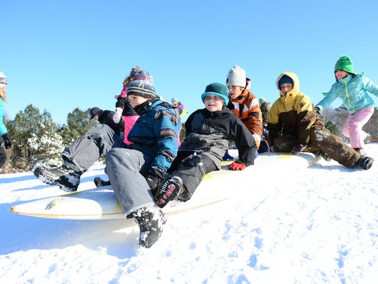 A group of kids sled down a hill on a snowy day.