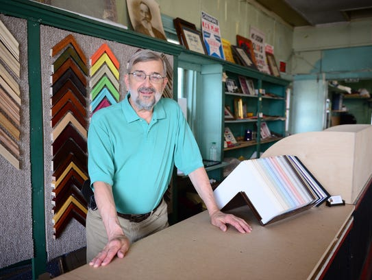 Ed Carey, co-owner of Carey's Frame Shop, stands behind
