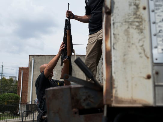 A round of rifles are loaded into a truck during a