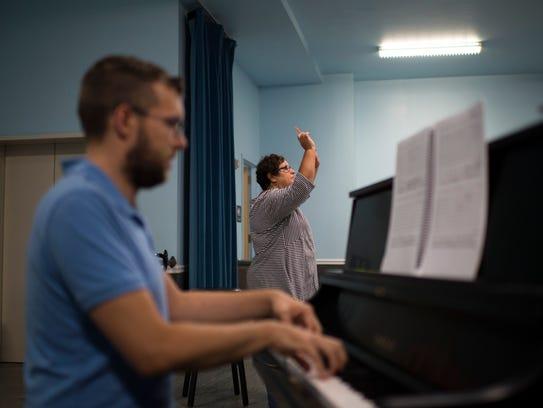 Maestra Liz Braden, right, conducts as principal pianist