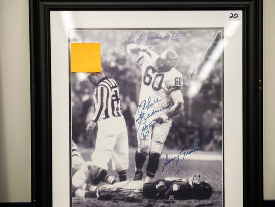 A signed picture of Eagles player Chuck Bednarik up for auction from the Burlington County Prosecutor's Office in Westampton. The photo was taken in 1960 immediately after Bednarik's legendary tackle of New York Giants quarterback Frank Gifford, who was knocked out, suffered a concussion and lay flat on the field.