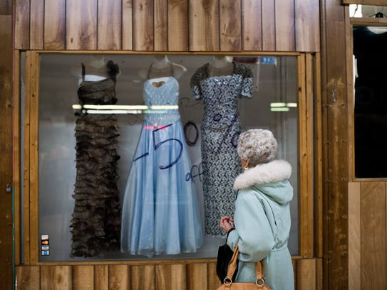 A shopper looks at dresses in a window Tuesday, Dec.