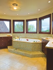 The master bath is mostly modern, with a soaking tub placed in a bay window alcove to take advantage of the wooded view.