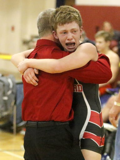 Cooper Rice of Oxford hugs his coach after holding