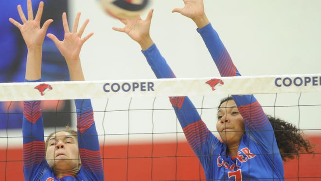 Cooper's Alexis Garcia (4) and Diamond Brown (7) defend at the net against a Lubbock Coronado shot. Coronado beat Cooper 28-26, 25-21, 25-20 in the District 4-5A match on Tuesday, Oct. 17, 2017 at Cougar Gym.
