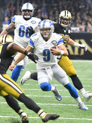 Lions quarterback Matthew Stafford breaks out of the collapsing pocket and goes up field on a run in the first quarter.