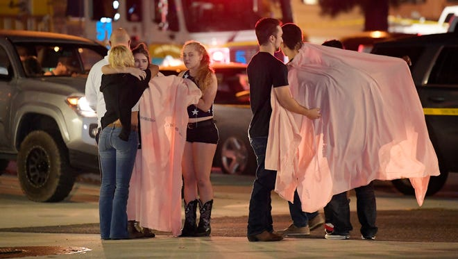 "People comfort each other as they stand near the scene Thursday in Thousand Oaks, Calif. where a gunman opened fire Wednesday inside a country dance bar crowded with hundreds of people on ""college night."""