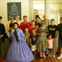 The DeLaGarza and Jones families shown here include Fort Stanton's 18,000th visitor of the year. Posing with them are Fort Stanton Inc. volunteer, Norm Ackerman, and Garrison volunteers Ken Davis (l), Sumi Ayami (m) and Kenny Walter (r).