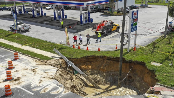 Florida Department of Transportation employees and on lookers checked out the sink hole at the intersection of SE 58th Avenue and SE Dogwood Road near the land fill at the Marathon gas station Monday morning, June 8, 2020. FDOT had traffic detouring around the sinkhole. The sink hole opened up early Sunday morning due to the heavy rains that Marion County experienced over the weekend. [Doug Engle/Ocala Star-Banner]2020