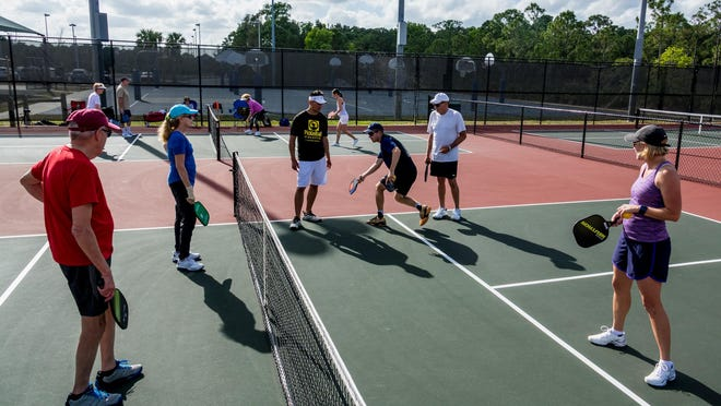 Top-ranked pickleball player Kyle Yates, from Ft. Myers, center, swinging, instructs players with local pro Eric Ah-Yuen, left, at the Russo Athletic Complex in Palm Beach Gardens on April 6, 2018.