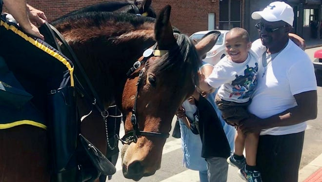 Jason Baker, 5, of Detroit, held by his father Johnny Baker, leans forward to pet Detroit Police 'horse 'Sal' during a warm and sunny day in Eastern Market in Detroit on Friday, May 25, 2018.