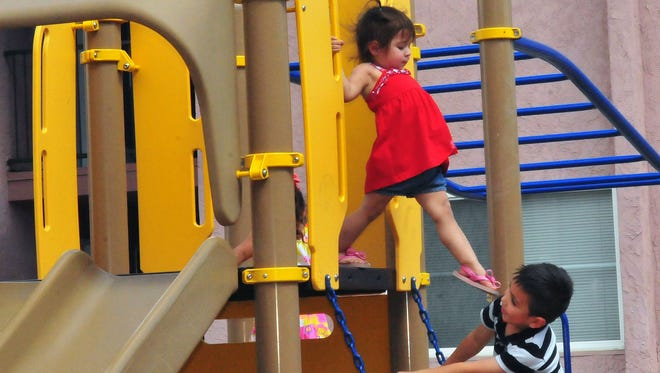 Christian Perez, 5, and Dariana Pina, 2 enjoy some playtime on the jungle gym Saturday afternoon at the Alto Tierra Apartments.  This photo taken June 4, 2016.