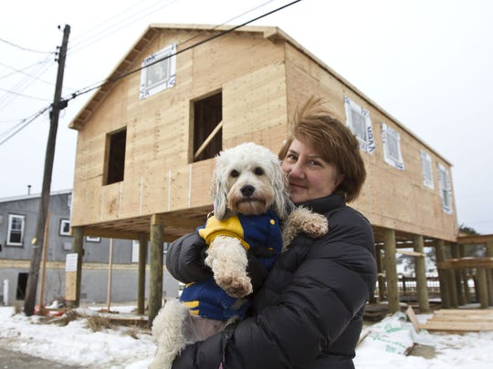 Kathy Gerndt of Bridgewater, holding her dog Sassy,  rebuilt her family's home in Ocean Beach 3, Toms River. JCP&L says the house is too close to the utility pole, so she must pay for a new one.