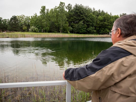 Happy Days Fishing Camp property owner Ron Stahl watches catfish feed Wednesday, June 27, 2018, in one of the camp's lakes.