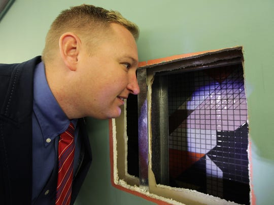 Cincinnati city council member Chris Seelbach looks through an access panel opening to see a portion of the huge mosaic tile mural by renowned Cincinnati artist Charley Harper at the Duke Energy Convention Center