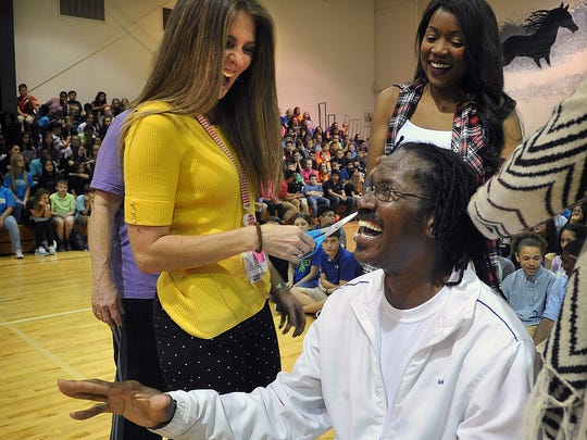 McNiel Middle School coach Russell Henry shares a laugh with teacher Lindsey Isgett before she cut off one of his 120 dreadlocks Friday afternoon. Henry has grown his hair to almost three feet long since 2004, and students and teachers paid $10 to cut each braid.