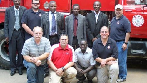 Former Norwalk Fire Chief Dustin Huston, picture in the front row second from the left, helped get a firetruck from Alaska to Katate, Zambia in the summer of 2014.