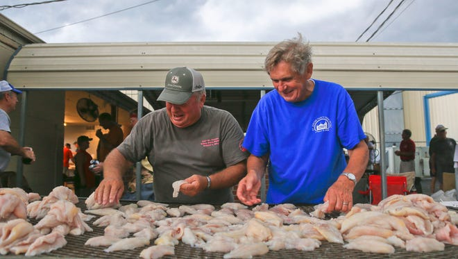 Dennis Wilson, left, and Leo Pindell separate fish for the fry Friday outside the Knights of Columbus hall in Fancy Farm, Ky.