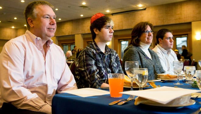 Rob and Marcey Propp of Cherry Hill, N.J.,  and their sons Zach, 19, (far right) and Matt, 15, attend a Passover Seder in 2013 at Temple Emanuel in Cherry Hill. The Propps are an interfaith family; Marcey Propp is Jewish and her husband Rob is Lutheran.