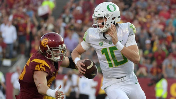 Nov 5, 2016; Los Angeles, CA, USA; Oregon Ducks quarterback Justin Herbert (10) is pressured by Southern California Trojans defensive end Porter Gustin (45) during a NCAA football game at Los Angeles Memorial Coliseum. Mandatory Credit: Kirby Lee-USA TODAY Sports