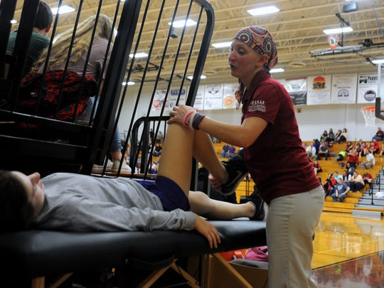 Crystal Shirk works with Warlassies basketball player Caitlyn Ledford as the Warhorses play on Jan. 20.