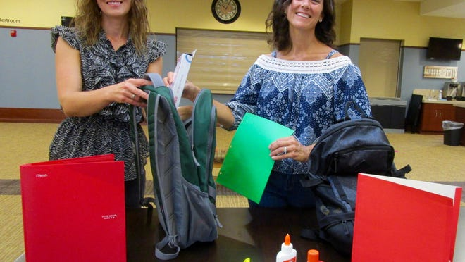 Yvette Biddle, left, director of discipleship at First United Methodist Church in Geneseo; and Andrea Masterson, a member of First United Methodist, show some of the filled backpacks that will be given to children in need in the Geneseo area. Photo by Claudia Loucks