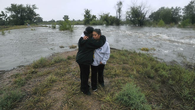Poudre River flood evacuee Claudia Flores, right, is comforted by daughter Leslie Zamora, 11, as the Poudre River floods near the Timberline Road  Road bridge just south of Mulberry Road in 2013.
