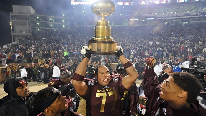 Mississippi State's Charles Siddoway holds the Egg Bowl trophy after State defeated Ole Miss 17 - 10 in Starkville late last year. Siddoway's draft status is in question after he and MSU defensive lineman Jordan Washington were arrested on burglary charges.