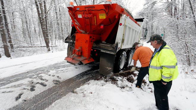 Two Alabama DOT employees work to free up a sand truck Tuesday, near Fort Payne, Ala.