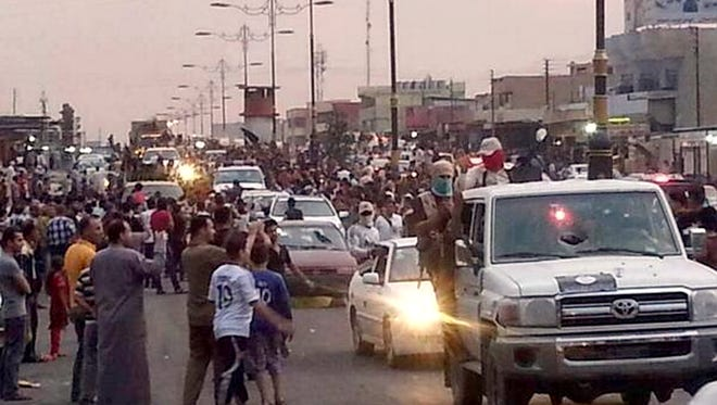 Militants parade down a main road in Mosul, Iraq, on June 11, 2014.  Iraqi officials say al-Qaeda-inspired militants who this week seized much of the country's Sunni heartland have pushed into an ethnically mixed province northeast of Baghdad, capturing two towns there.