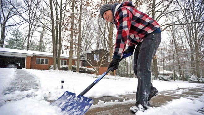 David Reitter shovels snow on the sidewalk of his home in State College, Pa., on Tuesday.  The first significant snowfall of the season fell overnight and continued through the morning.