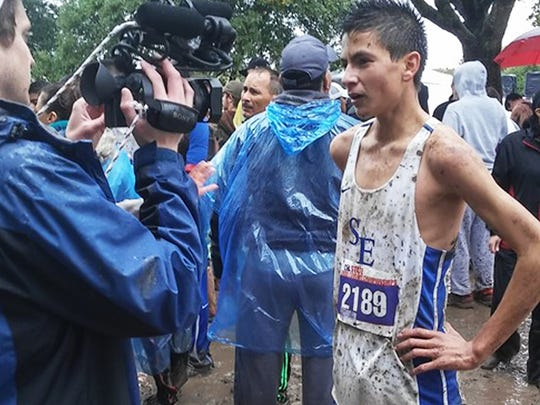 San Elizario junior Erick Arambula is interviewed after dominating the field and winning the individual gold in a time of 16:05.79 Saturday.