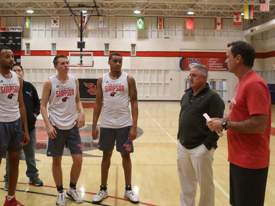 Simpson men's basketball coach Todd Franklin, from right, and assistant coach Mike Haworth talk with the team Monday after practice.