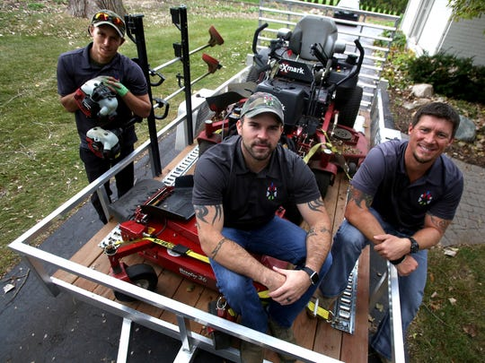 (L to R) James Harper, 21 of Newport with Stars and Stripes Lawn Care co-owners Chris Kamyszek, 30 of Troy and Mike Montecinos, 35 of Canton after they had finished cutting the grass at a client's home in Bloomfield Hills on Friday, October 9 2015. The company is based out of Troy works in collaboration with Plowz and Mowz giving on demand lawn and snow plowing service in Metro Detroit through an app that can be downloaded onto smartphones or desktop computers.