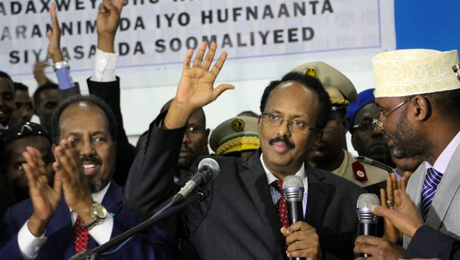 New Somali President Mohamed Abdullahi Farmajo, second right, waves to supporters as he is joined by incumbent President Hassan Sheikh Mohamud, left, after winning the election in Mogadishu, Somalia on Feb. 8, 2017.