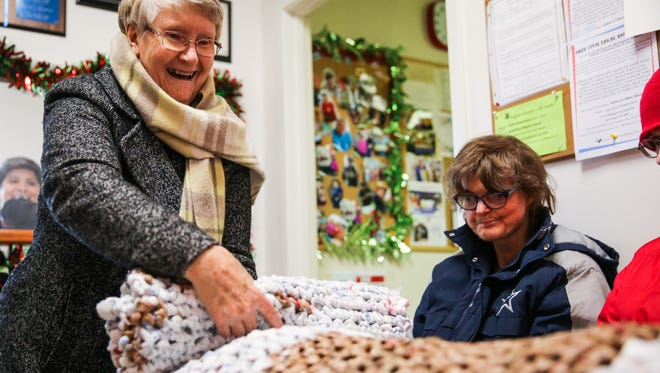 Mavis Bell, board member of Project Dignidad, unrolls a grocery-bag mat made by Mosaic clients and Calvary Lutheran Church volunteers for homeless people Thursday, Dec. 7, 2017, at Project Dignidad.