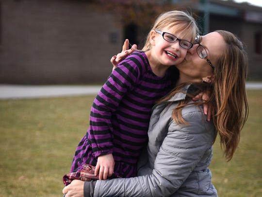 April Heide gets a kiss from her mom Cynamon Heide in front of Brown Elementary School in Reno on Nov. 20, 2015