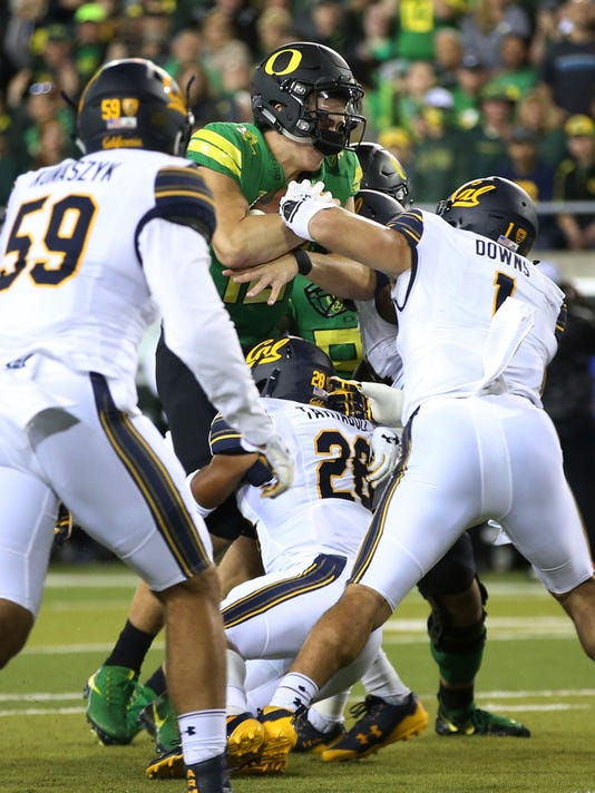 Oregon's Justin Herbert, center, drives into the end zone for a touchdown against California's Quentin Tartabull, bottom, and Devante Downs during the first quarter of an NCAA college football game Saturday, Sept. 30, 2017, in Eugene, Ore. (AP Photo/Chris Pietsch)