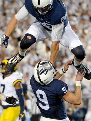 Penn State's Mike Gesicki leap-frogs quarterback Trace McSorley in celebration of McSorley's touchdown in the first half of an NCAA Division I college football game Saturday, Oct. 21, 2017, at Beaver Stadium. The No. 2 Penn State Nittany Lions defeated Michigan 42-13, improving their season record to 7-0.